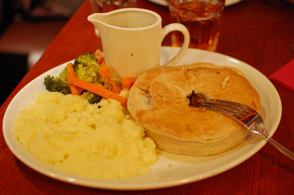 Traditional pub dinner of beef pie, mashed potatoes, and a few veggies. The little pot contains gravy! British cuisine is often the subject of ridicule, but I go for this sort of old-fashioned comfort food. (Hey, chicken pot pies got me through grad school.)